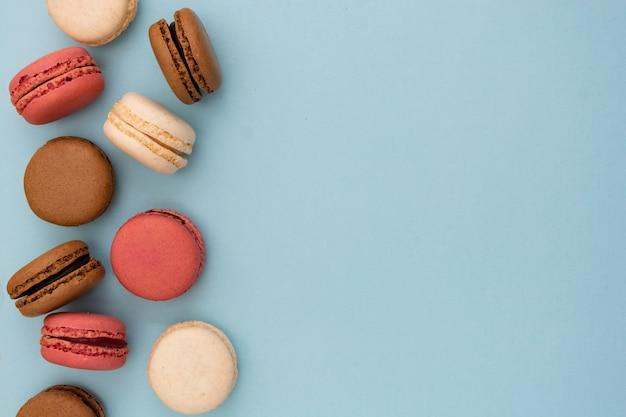 Macarons bolos em linha sobre fundo azul. walpapper de mídia social plana leigos.