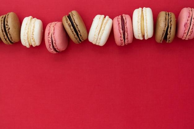 Macarons bolos sobre fundo vermelho. postura plana. copie o espaço.