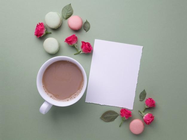 Macarons, café e rosa sobre fundo verde. vista do topo. postura plana