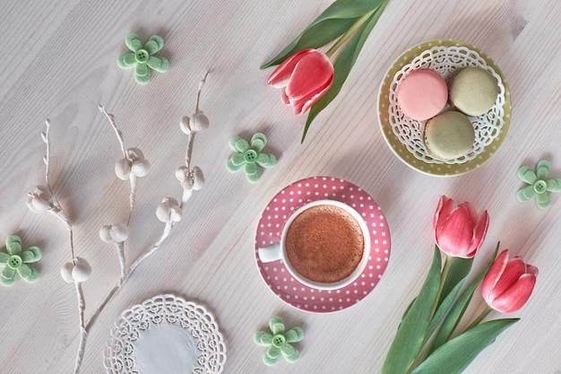 Macarons, café expresso em copo rosa, frésias e tulipa rosa, vista superior