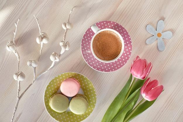 Macarons, café expresso em copo rosa, frésias e tulipas cor de rosa