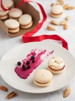Macarons caseiros com recheio de groselha. amêndoas, bagas de groselha e recheio de biscoitos em um prato.