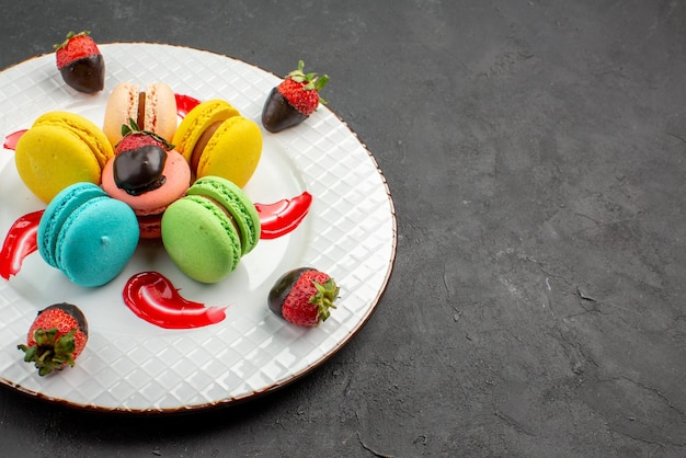 Macarons coloridos com morangos e chocolate