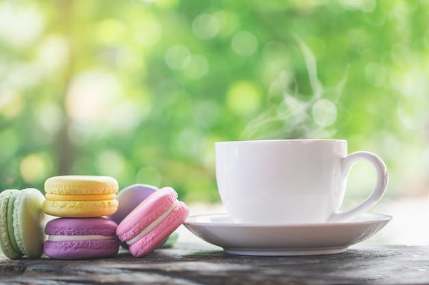Macarons coloridos com xícara de café quente