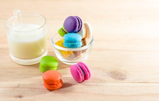 Macarons coloridos em copo transparente na mesa sobre fundo de madeira