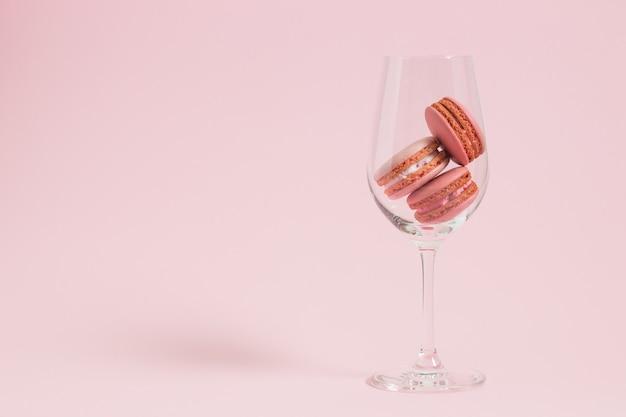 Macarons coloridos em fundo rosa