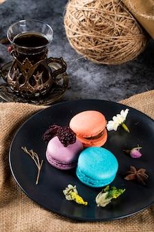Macarons coloridos em um pires preto e um copo de chá em uma serapilheira rústica.