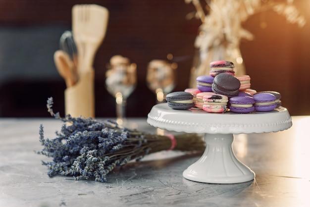 Macarons coloridos em uma bandeja branca em uma mesa de mármore com um guardanapo, lavanda e acessórios de cozinha.
