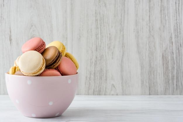 Macarons coloridos em uma tigela vintage na mesa de madeira branca