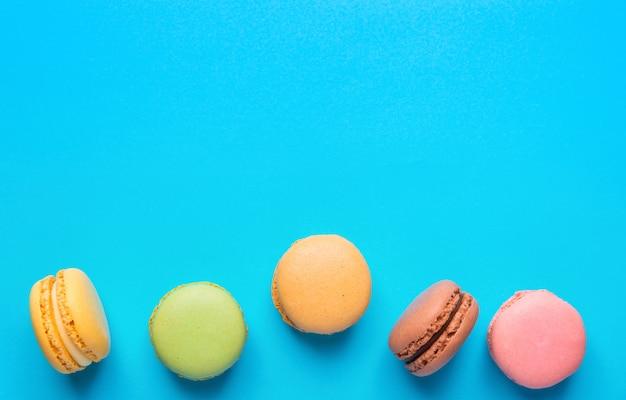 Macarons coloridos espalhados sobre fundo azul