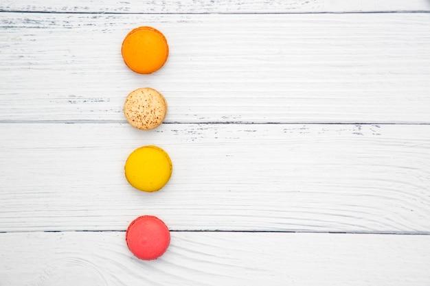 Macarons coloridos sobre fundo branco de madeira