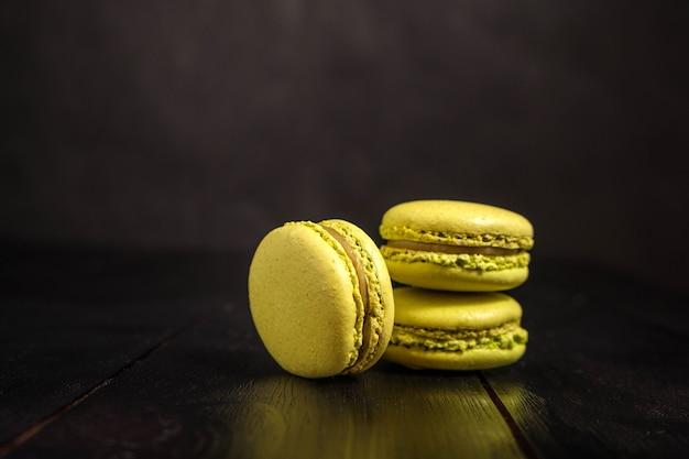 Macarons com sabor de pistache em uma mesa escura