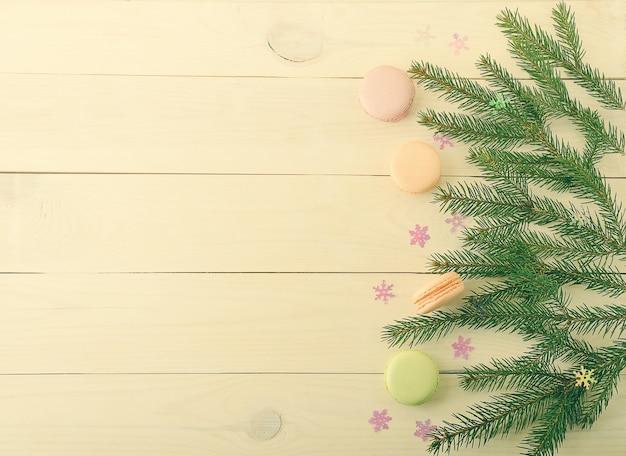 Macarons de bolo com galhos de árvores de natal e flocos de neve em fundo de madeira