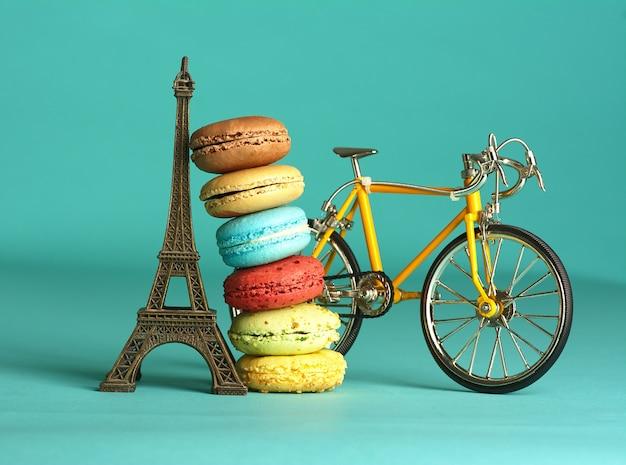 Macarons de diferentes sabores recarregados na torre eiffel e uma bicicleta