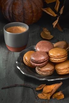 Macarons de outono com caramelo e cacau com café na madeira rústica escura