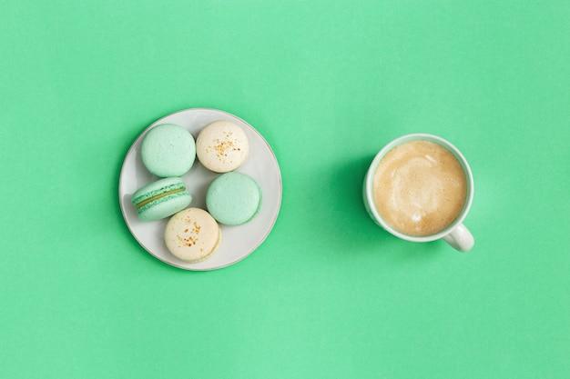 Macarons deliciosos e cappuccino de café quente em caneca grande sobre fundo azul brilhante