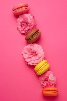 Macarons doces multicoloridos com botões de creme e rosa