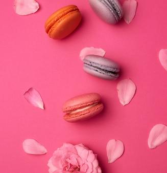 Macarons doces multicoloridos com creme e um botão de rosa com pétalas espalhadas