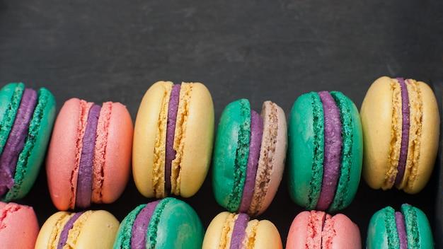 Macarons doces na mesa escura retrô. vista superior, conceito de padaria de tempo de férias.