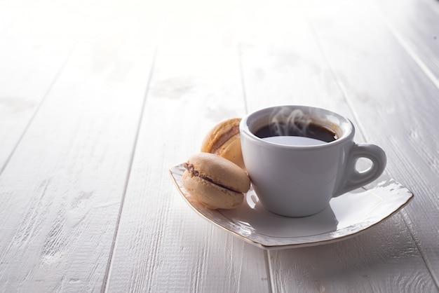 Macarons doces saborosos e copo de café. bolinhos de amêndoa no fundo de madeira branco. copie espaço