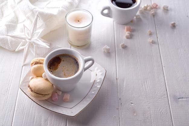 Macarons doces saborosos e xícara de café sobre fundo branco de madeira