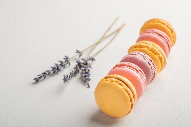 Macarons e flores de lavanda na superfície branca, sobremesas francesas coloridas seletivas
