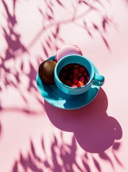 Macarons e xícara de chá com sombras na superfície rosa