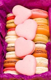 Macarons franceses coloridos com corações em fundo violeta