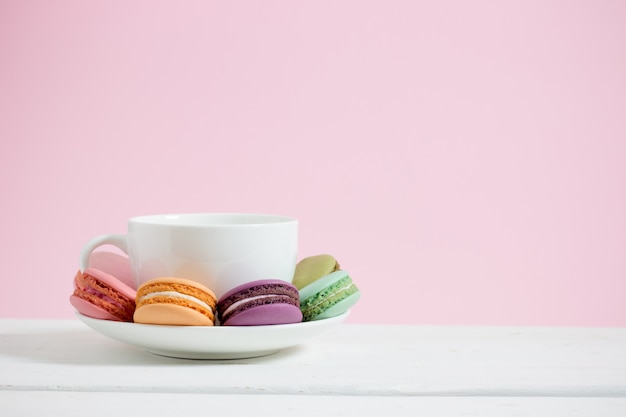 Macarons franceses coloridos e copo de café branco no fundo de madeira do rosa pastel da tabela branca.