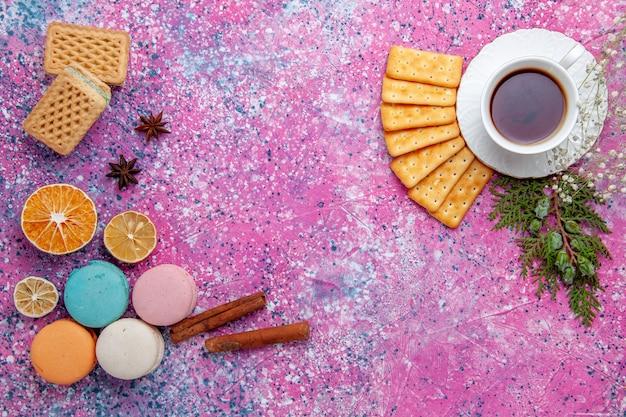 Macarons franceses com biscoitos waffles e uma xícara de chá na mesa rosa