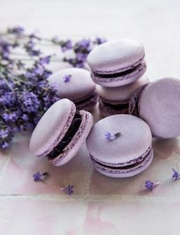 Macarons franceses com sabor de lavanda e flores frescas de lavanda em um fundo de ladrilho