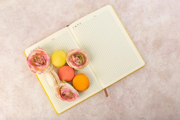 Macarons franceses com vista de cima e rosas no caderno e bolo de mesa rosa com açúcar doce