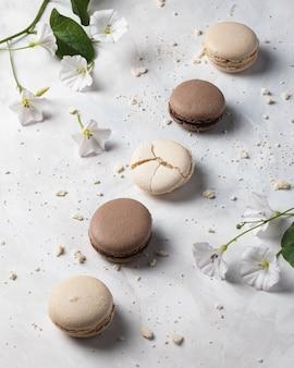 Macarons franceses de baunilha e chocolate com flores na superfície branca. sobremesa francesa.