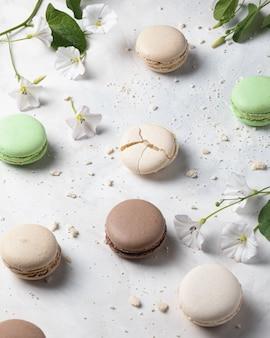 Macarons franceses de baunilha, pistache e chocolate com flores na superfície branca. sobremesa francesa.