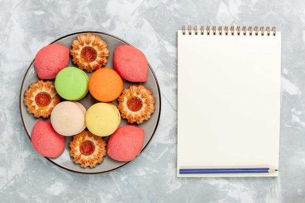 Macarons franceses de cima com biscoitos e bloco de notas em uma superfície branca clara