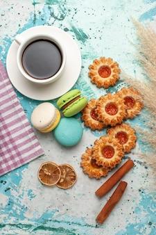 Macarons franceses de cima com biscoitos e uma xícara de chá na superfície azul
