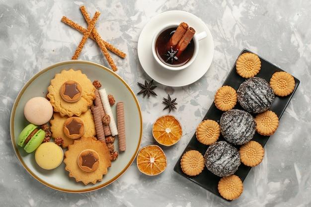Macarons franceses de cima com bolos de chocolate e biscoitos na superfície branca.