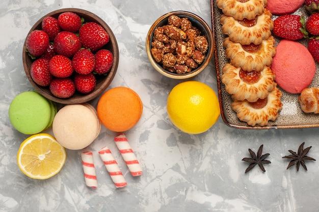 Macarons franceses de cima com morangos vermelhos frescos e biscoitos na superfície branca