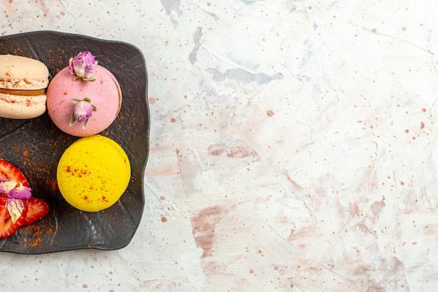 Macarons franceses de cima dentro do prato em uma mesa branca, bolo de biscoito, fruta doce