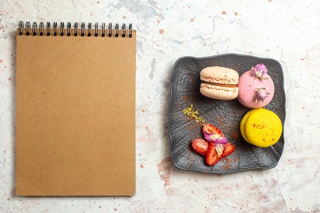 Macarons franceses de cima dentro do prato na mesa branca bolo de biscoito com frutas doces