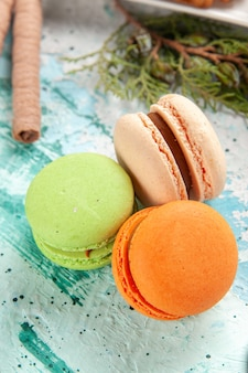 Macarons franceses de frente, deliciosos bolinhos na superfície azul-clara