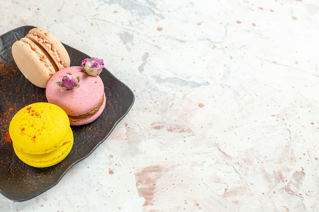 Macarons franceses de frente para dentro do prato no bolo doce de biscoito de mesa branca