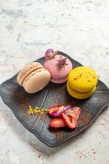 Macarons franceses de frente para dentro do prato no bolo doce de biscoito de mesa branco