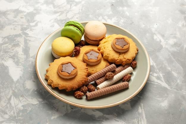 Macarons franceses de vista frontal com bolinhos e biscoitos na superfície branca