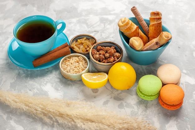 Macarons franceses de vista frontal com uma xícara de chá e bagels em biscoitos de bolacha de mesa branca
