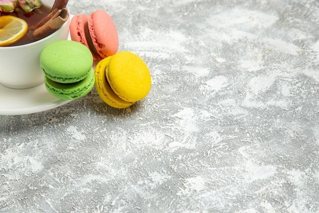 Macarons franceses de vista frontal com uma xícara de chá na superfície branca biscoito açúcar bolo doce assar biscoito