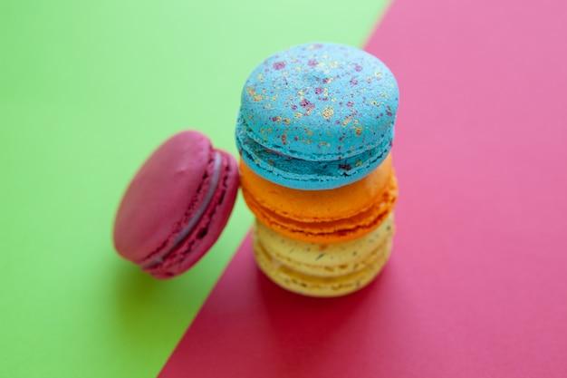 Macarons franceses. pilha de biscoito colorido sobre fundo verde e vermelho
