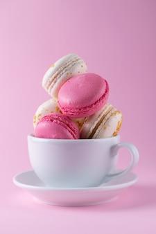Macarons franceses saborosos de cores rosa e brancos e sabores diferentes em um copo branco