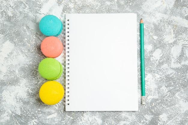 Macarons ful de bolos franceses de vista superior com bloco de notas na superfície branca