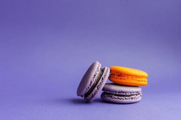 Macarons multicoloridos sobre um fundo roxo. sobremesa francesa para o halloween. produtos de panificação de farinha de amêndoa.